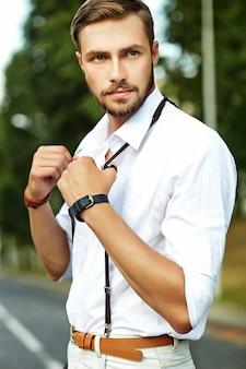 Hombre guapo modelo hipster en ropa de verano elegante posando