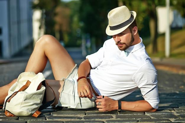 Hombre guapo modelo hipster en ropa de verano elegante sentado en el sombrero con bolsa