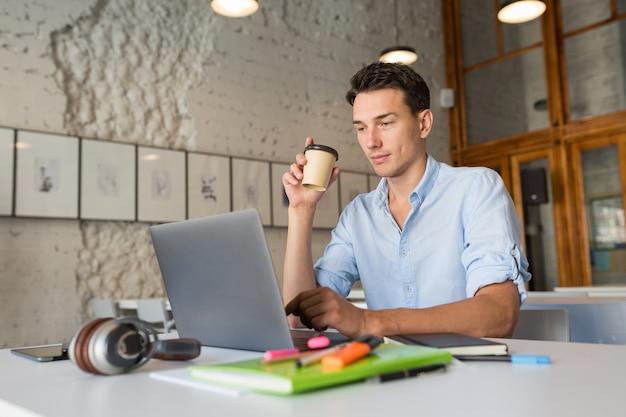 Hombre guapo moderno ocupado en su trabajo tomando café