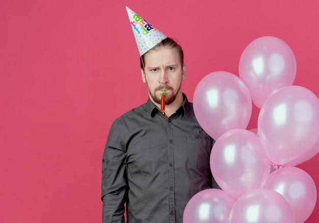 Hombre guapo molesto en gorro de cumpleaños se encuentra con globos de helio que soplan silbato aislado en la pared rosa
