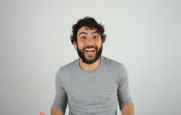 Hombre guapo morena alegre con barba y pelo rizado retrato de estudio