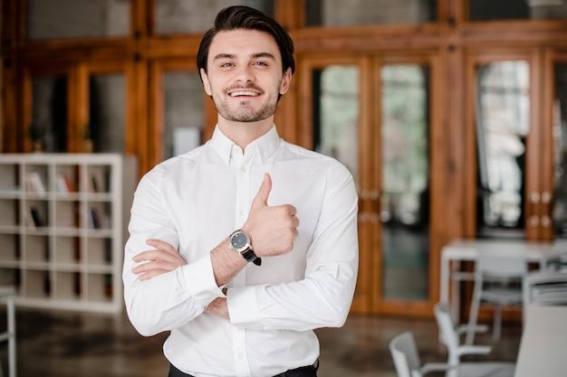Hombre guapo mostrando los pulgares hacia arriba y sonriendo