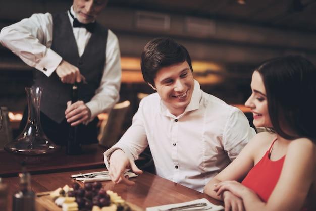 Hombre guapo y mujer en fecha en restaurante.