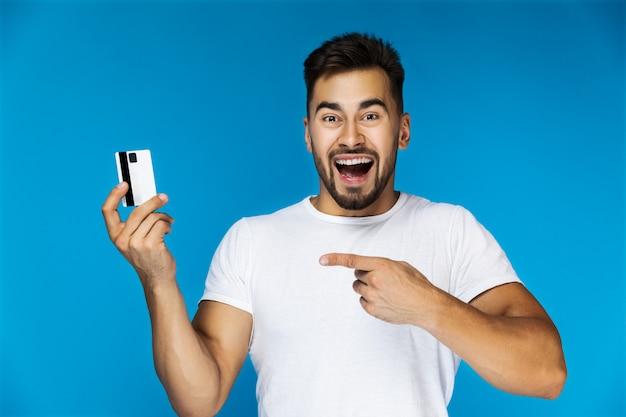 Hombre guapo muy emocional muestra su tarjeta de crédito