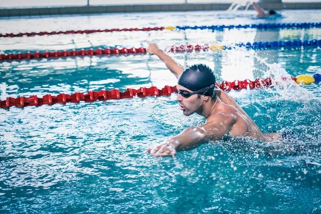 Hombre guapo nadando en la piscina
