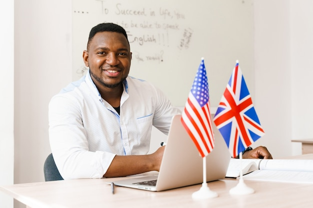 Hombre guapo negro usa su computadora portátil para el trabajo en línea de acuerdo con el distanciamiento social