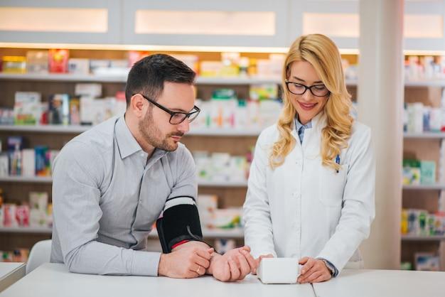 Hombre guapo obtener su presión arterial medida en una tienda de productos farmacéuticos.