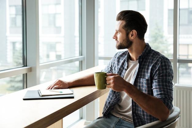 Hombre guapo en oficina coworking mientras escribía notas