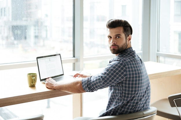 Hombre guapo en la oficina coworking mientras usa la computadora portátil