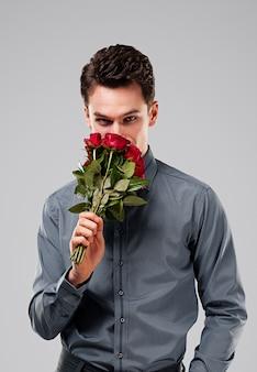 Hombre guapo oliendo ramo de rosas rojas