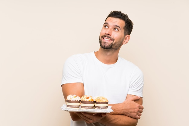 Hombre guapo con pastel de muffin sobre fondo aislado