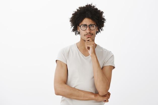 Hombre guapo pensativo escéptico en gafas mirando, reflexionando, haciendo elección