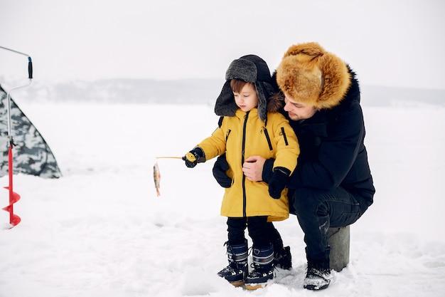 Hombre guapo en una pesca de invierno con su pequeño hijo