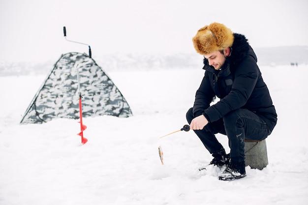 Hombre guapo en una pesca de invierno