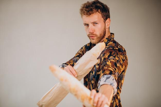 Hombre guapo de pie con baguettes francesas