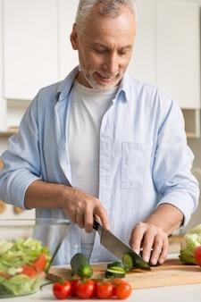 Hombre guapo de pie en la cocina usando laptop y cocina