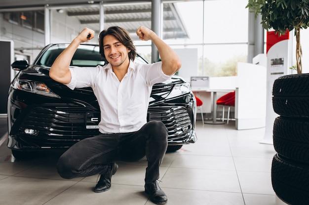 Hombre guapo de pie delante de un automóvil en una sala de exposición de automóviles