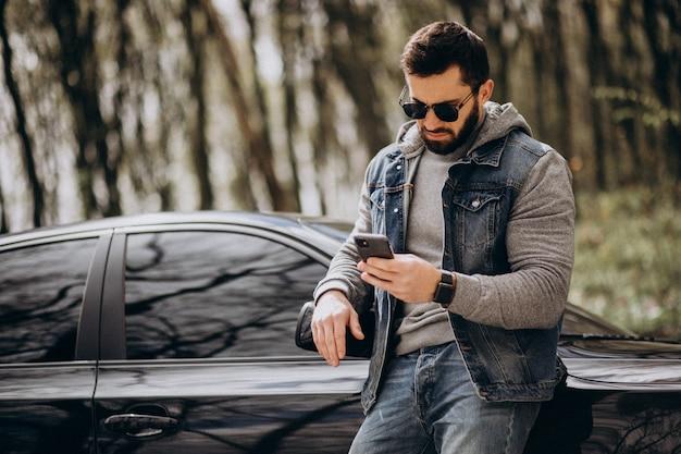 Hombre guapo de pie junto al coche en el parque