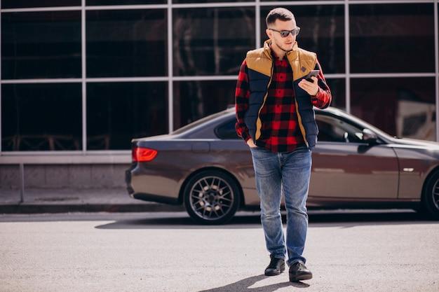 Hombre guapo de pie junto al coche