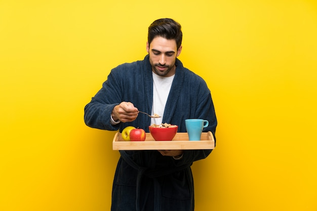 Hombre guapo en pijama sobre pared amarilla aislada
