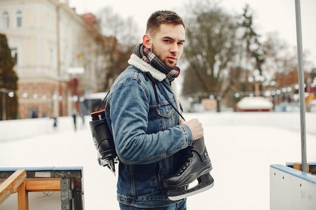Hombre guapo en una pista de hielo con skate
