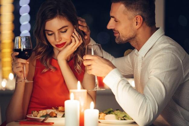 Hombre guapo planchar a su novia mientras cena romántica en la noche