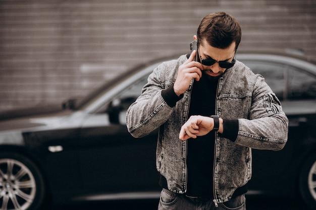 Hombre guapo posando junto al coche en la calle