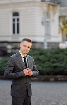 Hombre guapo posando en traje de boda en las calles