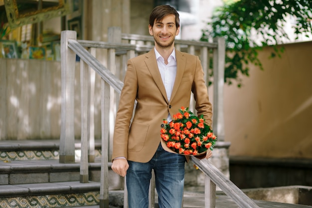 Hombre guapo con ramo de rosas hablando feliz por teléfono