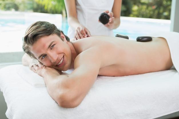 Hombre guapo recibiendo masaje con piedras en el centro de spa