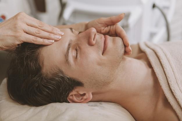 Hombre guapo recibiendo tratamiento facial de cuidado de la piel