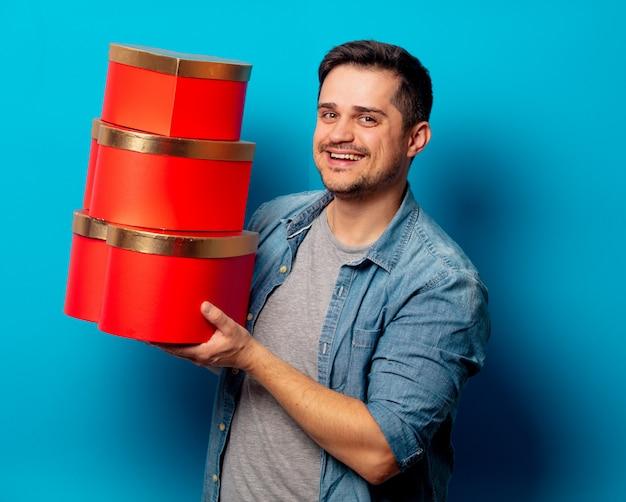 Hombre guapo con regalos rojos