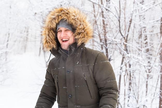 Hombre guapo en retrato sonriente de sombrero de invierno en la naturaleza nevada.