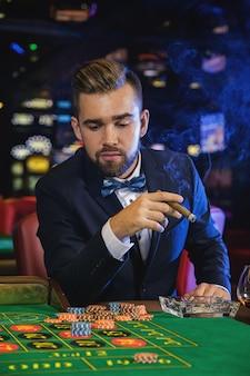 Hombre guapo rico fumando cigarros en el casino