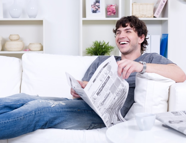 Hombre guapo riendo feliz en casuals tumbado en el sofá con periódico - en el interior