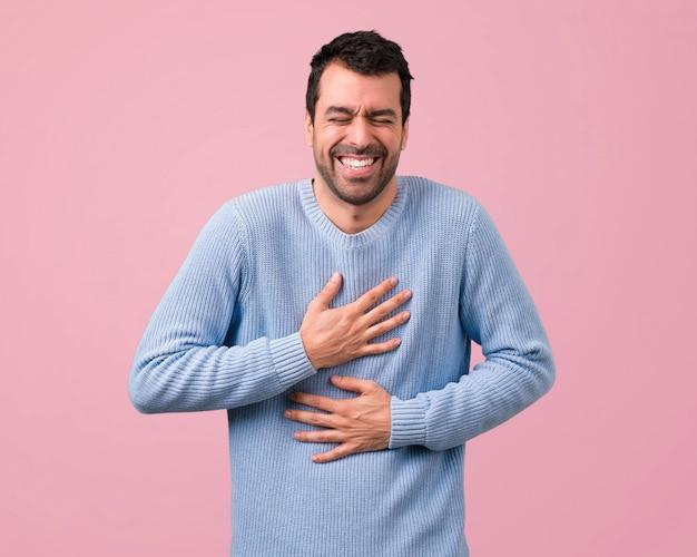 Hombre guapo riendo sobre fondo rosa