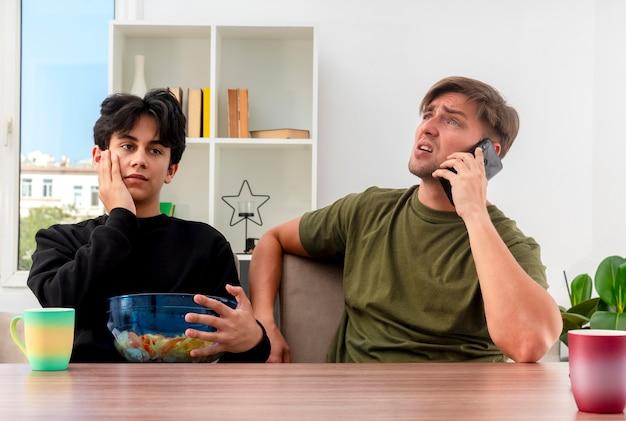 Hombre guapo rubio joven disgustado hablando por teléfono sentado en la mesa con chico guapo morena joven decepcionado poniendo la mano en la cara sosteniendo un tazón de patatas fritas dentro de la sala de estar de diseño