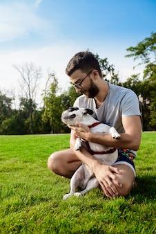 Hombre guapo sentado con bulldog francés sobre césped en el parque