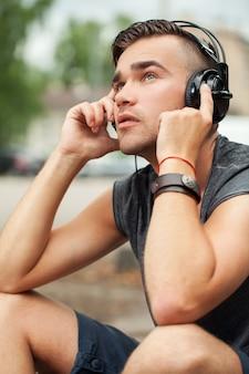 Hombre guapo sentado en la calle con auriculares