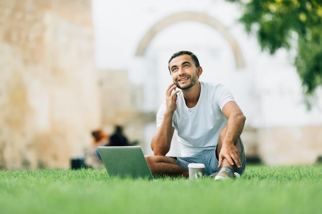 Hombre guapo sentado en el césped de la ciudad con una computadora portátil y hablando por teléfono