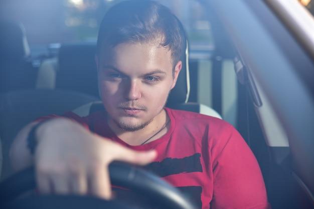 Hombre guapo sentado en un coche y sosteniendo el volante.