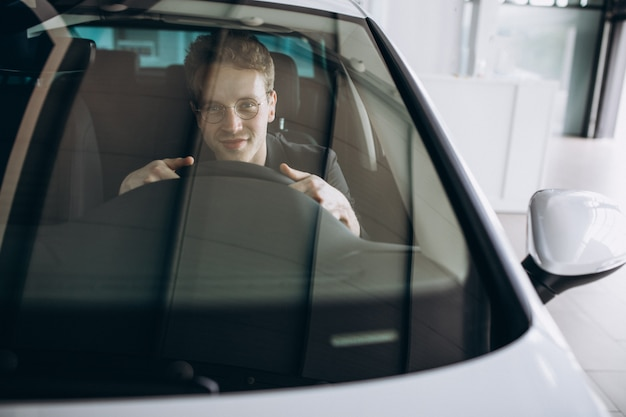 Hombre guapo sentado en un coche