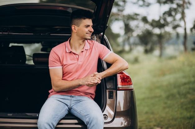 Hombre guapo sentado en la parte trasera del auto
