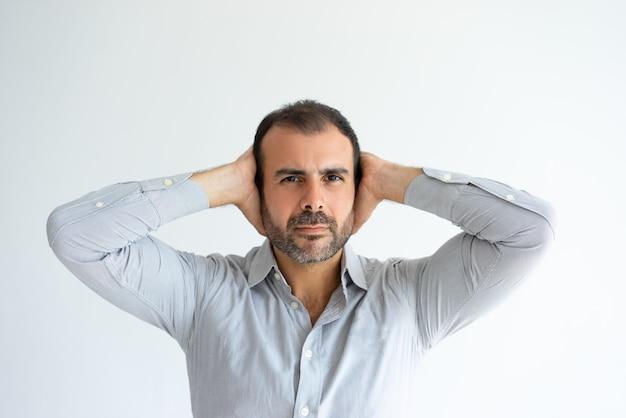 Hombre guapo serio que cubre las orejas con las manos