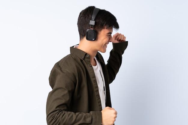 Hombre guapo sobre pared azul escuchando música y bailando
