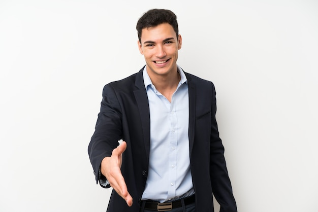 Hombre guapo sobre pared blanca aislada apretón de manos después de buen trato