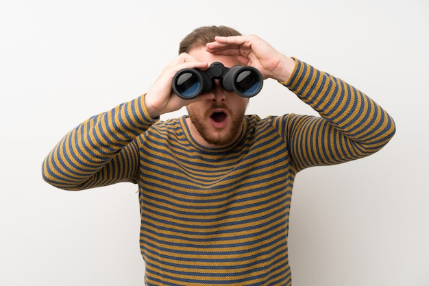 Hombre guapo sobre pared blanca aislada con binoculares negros