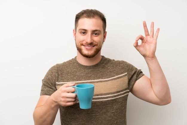 Hombre guapo sobre pared blanca aislada con taza de café caliente