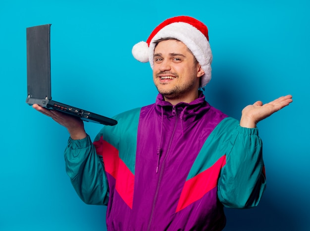 Hombre guapo con sombrero de navidad y chaqueta de los años 90 con laptop