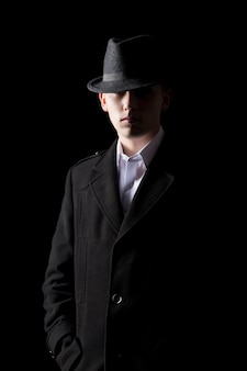 Hombre guapo en sombrero en la oscuridad